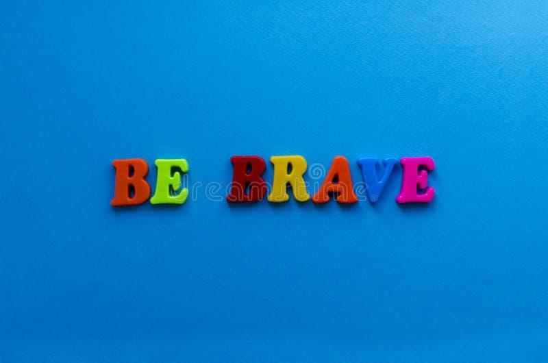 De tekst moedig is van plastiek kleurde brieven op blauwe document achtergrond stock fotografie