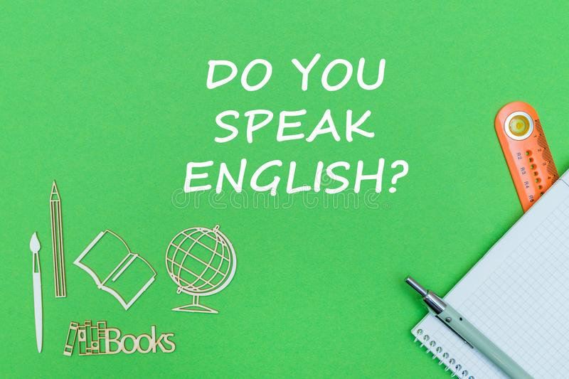 De tekst u spreekt het Engels, de houten miniaturen van de schoollevering, notitieboekje op groene achtergrond stock afbeelding