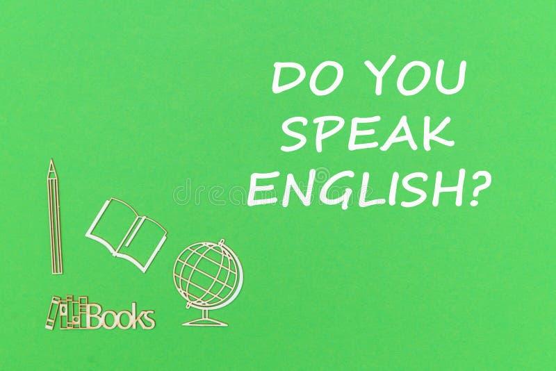 De tekst u spreekt het Engels, de houten miniaturen van de schoollevering op groene achtergrond stock foto's