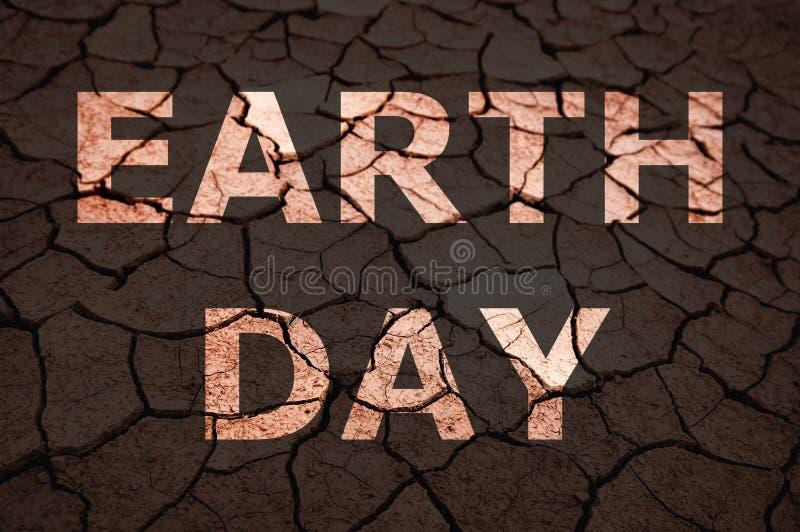 De tekst van de aardedag op droge grond stock foto