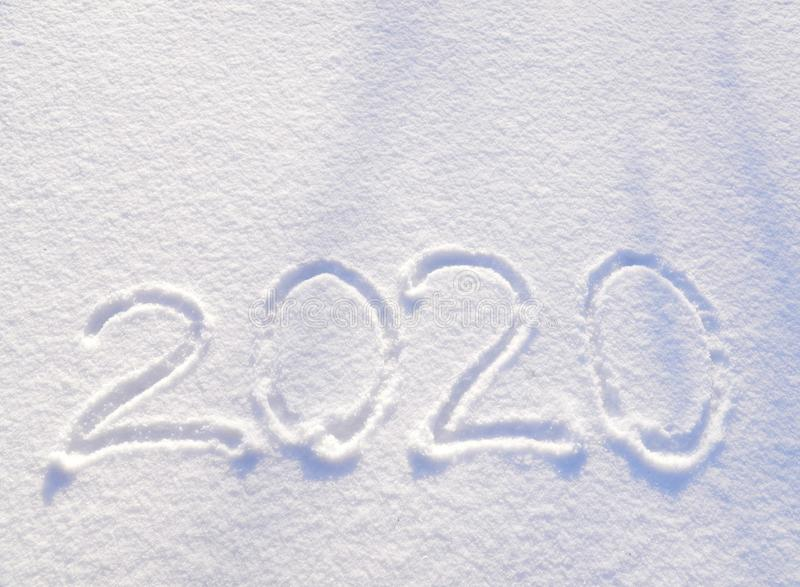 de tekst van 2020 die op de achtergrond van verse sneeuwtextuur wordt geschreven - de wintervakantie, Vrolijke Kerstmis, de Zonni stock afbeeldingen