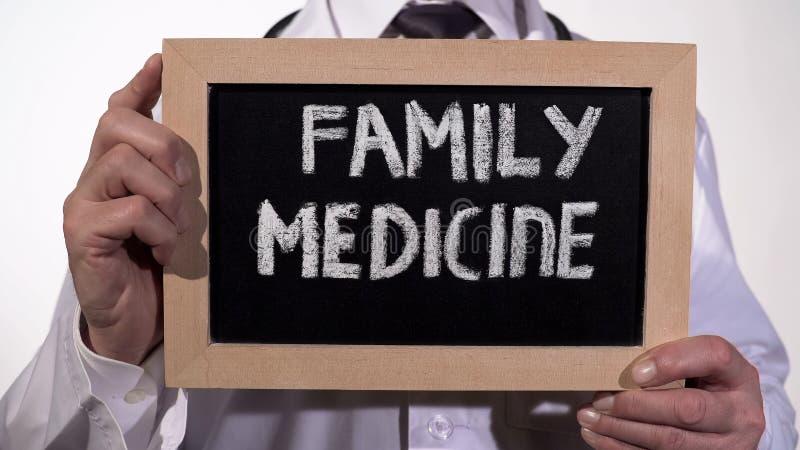 De tekst van de familiegeneeskunde op bord in artsenhanden, uitvoerige gezondheidszorg stock foto