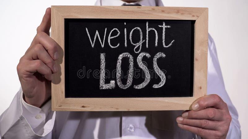 De tekst van het gewichtsverlies op bord in artsenhanden, gezonde voedingaanbevelingen royalty-vrije stock fotografie