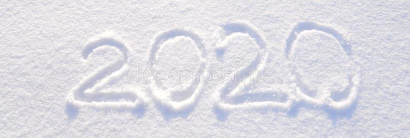 de tekst van 2020 op de achtergrond van verse sneeuwtextuur wordt geschreven - de wintervakantie, Vrolijke Kerstmis, de Zonnige d royalty-vrije stock afbeelding