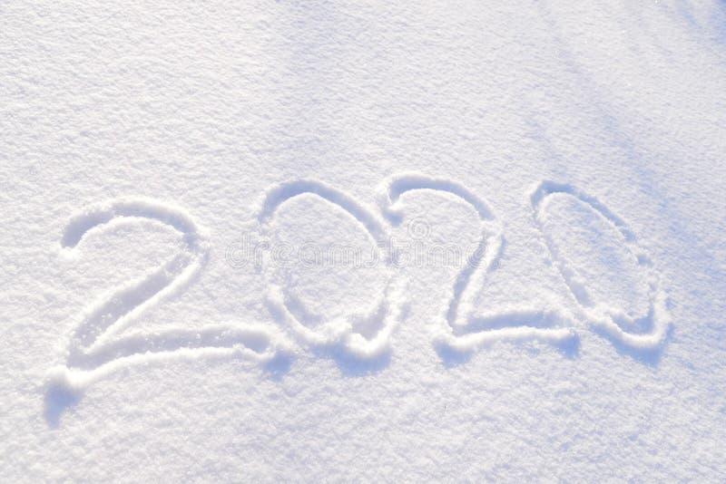 de tekst van 2020 op de achtergrond van verse sneeuwtextuur wordt geschreven - de wintervakantie, Vrolijke Kerstmis, de Zonnige d royalty-vrije stock fotografie