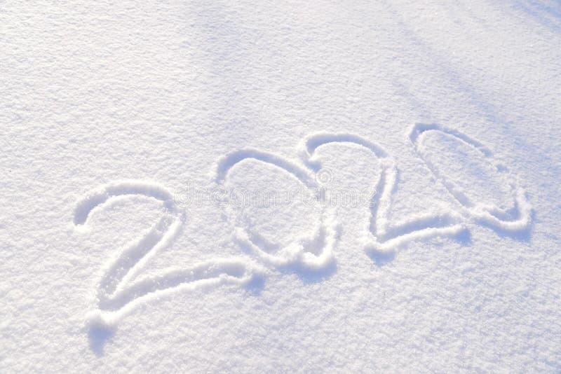 de tekst van 2020 op de achtergrond van verse sneeuwtextuur wordt geschreven - de wintervakantie, Vrolijke Kerstmis, de Zonnige h stock foto's