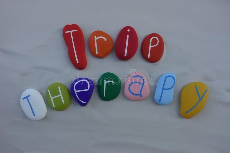 De tekst van de reistherapie met gekleurde stenen over wit zand stock foto's