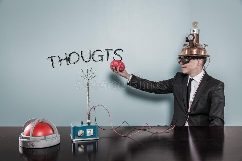 De Tekst van zakenmanwearing helmet holding Brain While Sitting By Thoughts royalty-vrije stock foto's