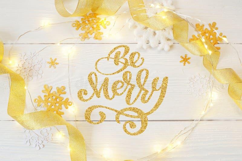 De tekst Vrolijk is in Kerstmisslinger van slingers en sneeuwvlokken op een houten achtergrond Fotografie voor vakantiegroet stock foto