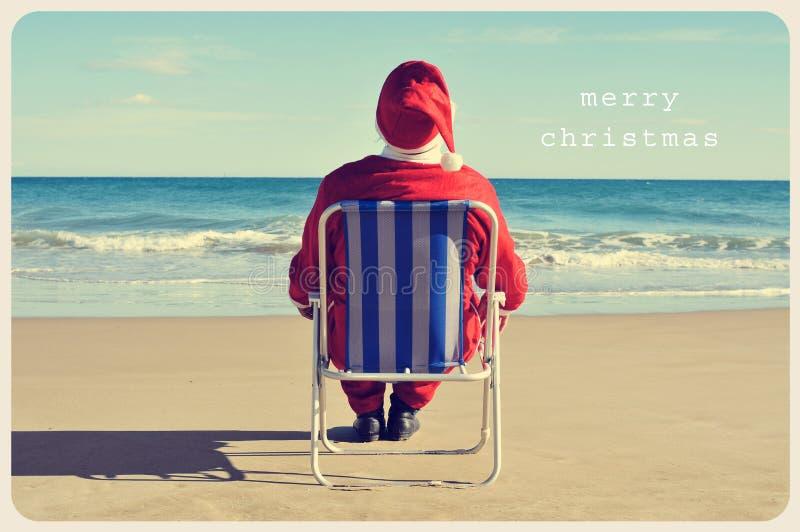 De tekst vrolijke Kerstmis en Kerstman op het strand royalty-vrije stock foto's