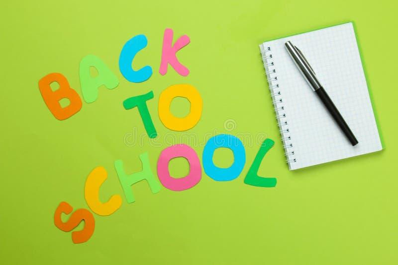 De tekst zal naar de school van multicolored brieven en een notitieboekje met een pen op een heldergroene achtergrond zijn terugg stock foto