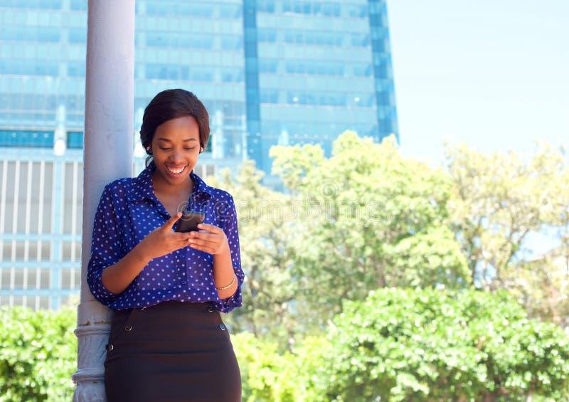 De tekstbericht van de bedrijfsvrouwenlezing op mobiele telefoon in openlucht stock afbeeldingen