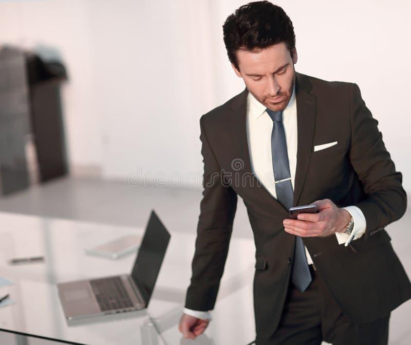 De tekstbericht van de zakenmanlezing op smartphone, terwijl status in het bureau stock foto