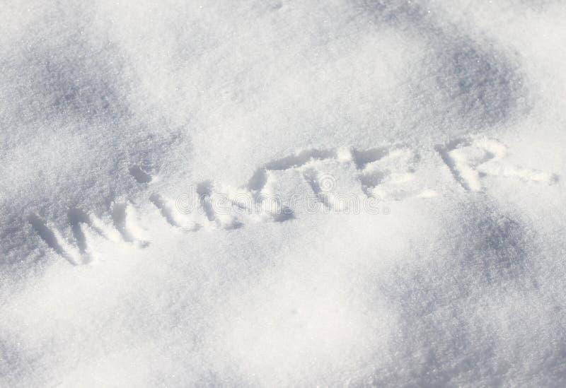 De tekstwinter in de witte sneeuw Handschrift de woordwinter in de sneeuw Sneeuw achtergrondtextuur en koud de winterconcept De h royalty-vrije stock foto's