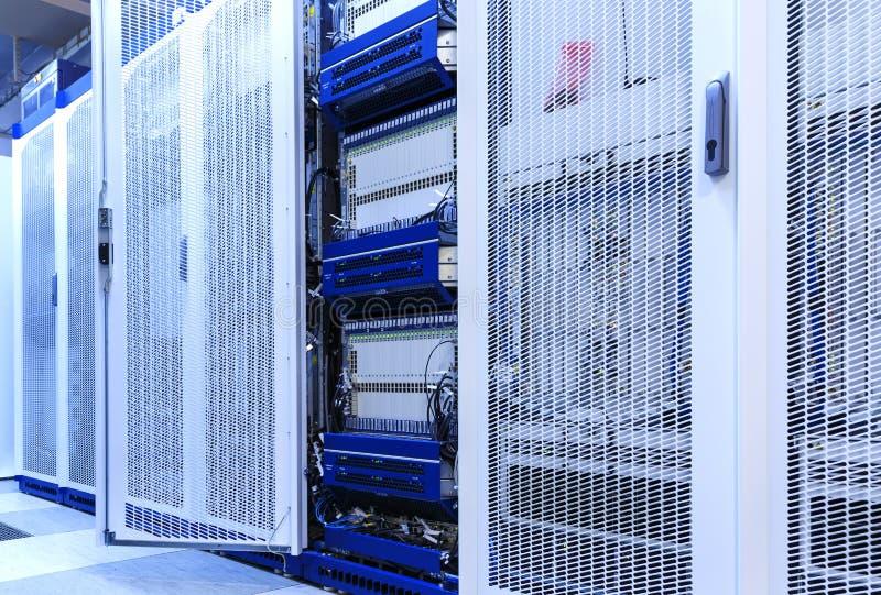 De telecommunicatie-uitrusting met vele kabels, de schakelaars en de airconditioners in moderne mededelingen centreren stock afbeeldingen