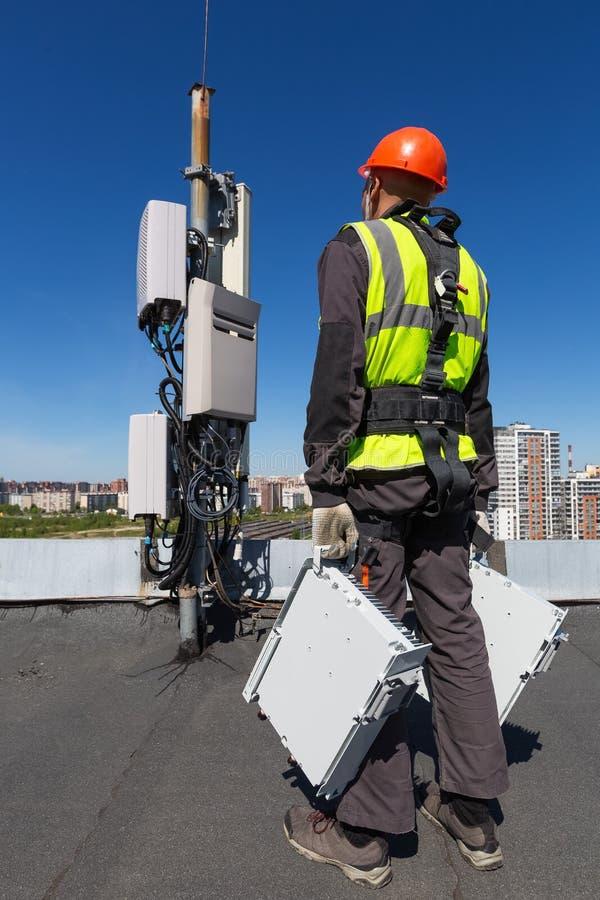De telecommunicatieingenieur in helm en eenvormig houdt telecomunicationmateriaal in zijn hand en antennes van GSM DCS royalty-vrije stock afbeeldingen