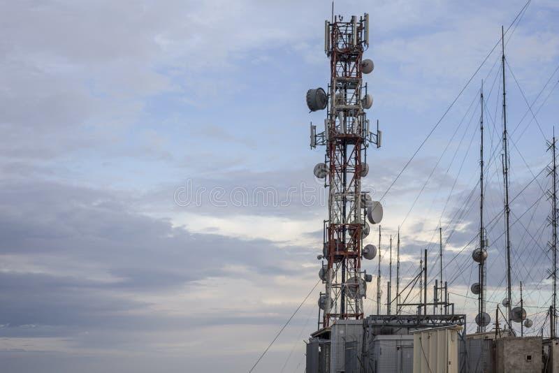 De telecommunicatietoren die veelvoudige antennes houden hield dichtbij aan veelvoudige paneeldozen Er zijn kabel-gebleven torens stock foto
