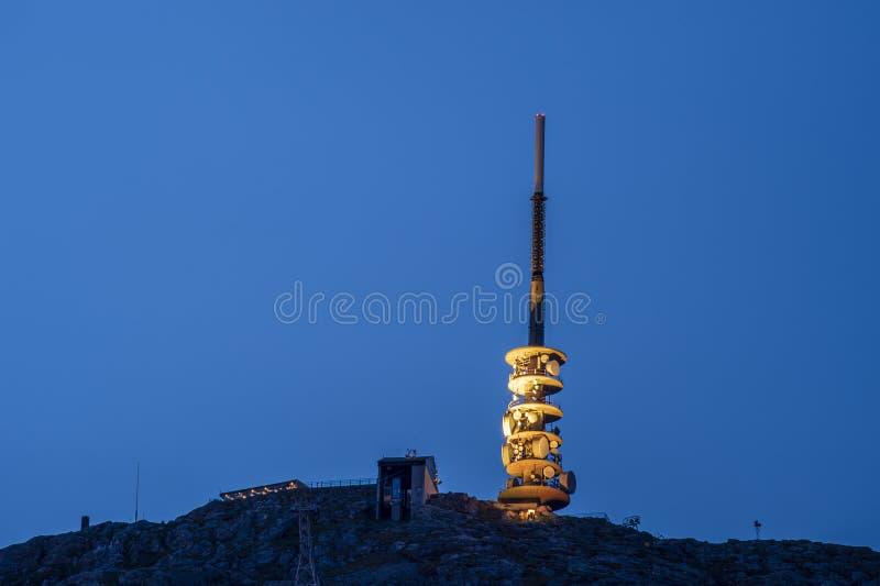 De telecommunicatietoren omhoog met geel wordt aangestoken colorised licht tegen een blauwe hemel die royalty-vrije stock foto