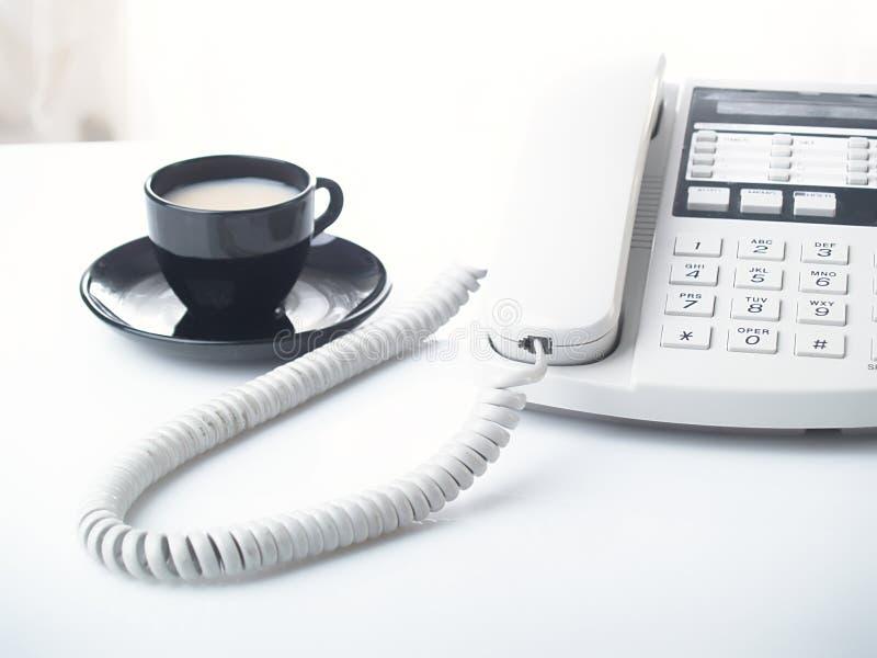 De telefoon en de kop van het bureau stock afbeelding