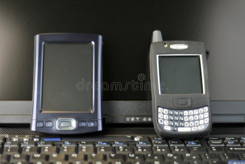 De telefoon van de cel en rust PDA op een laptop toetsenbord stock foto's