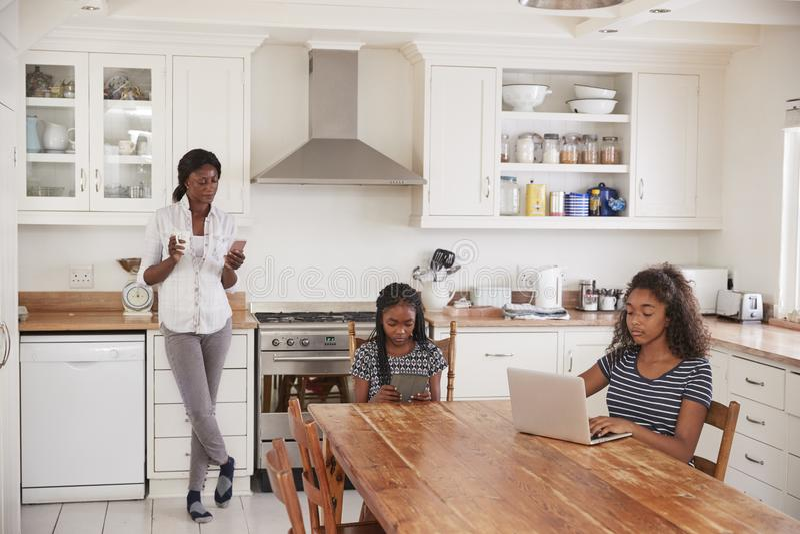 De Telefoon van het moedergebruik als Dochters Sit At Table Doing Homework royalty-vrije stock fotografie