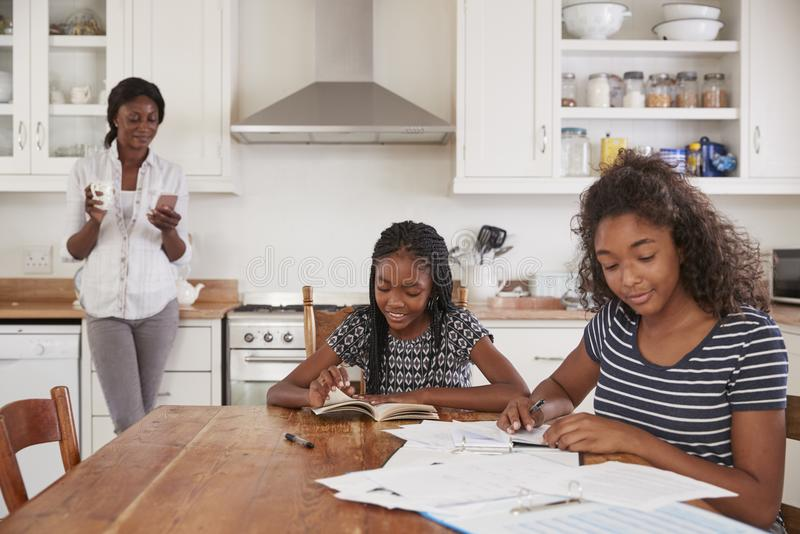 De Telefoon van het moedergebruik als Dochters Sit At Table Doing Homework royalty-vrije stock foto