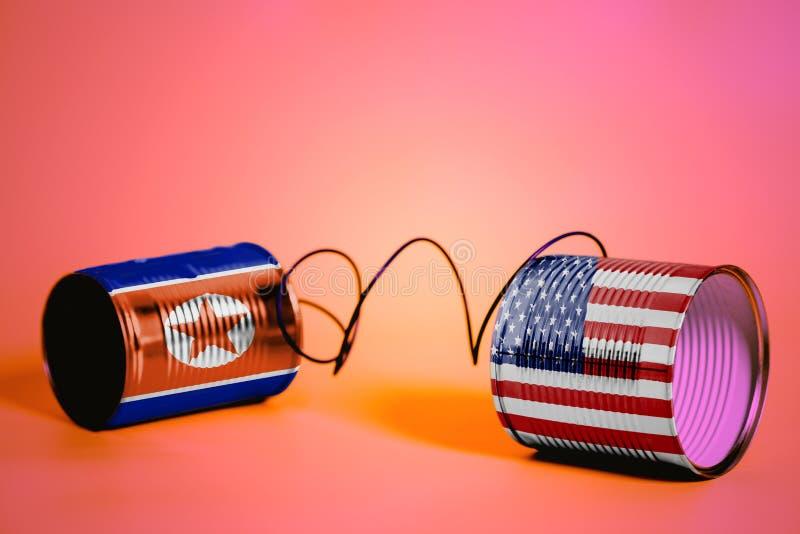 De telefoon van het tinblik met de Vlaggen van de V.S. en van Noord-Korea Communicatie concept stock foto