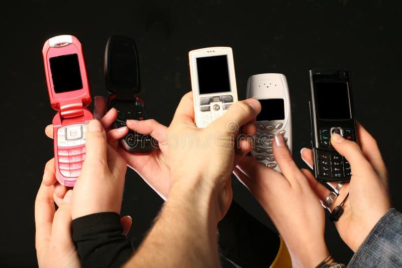 De telefoons van de cel in handen