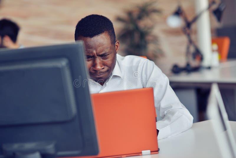 De teleurgestelde Afrikaanse zakenman wordt duizelig gemaakt en door een fout in officiële documenten verward royalty-vrije stock afbeeldingen