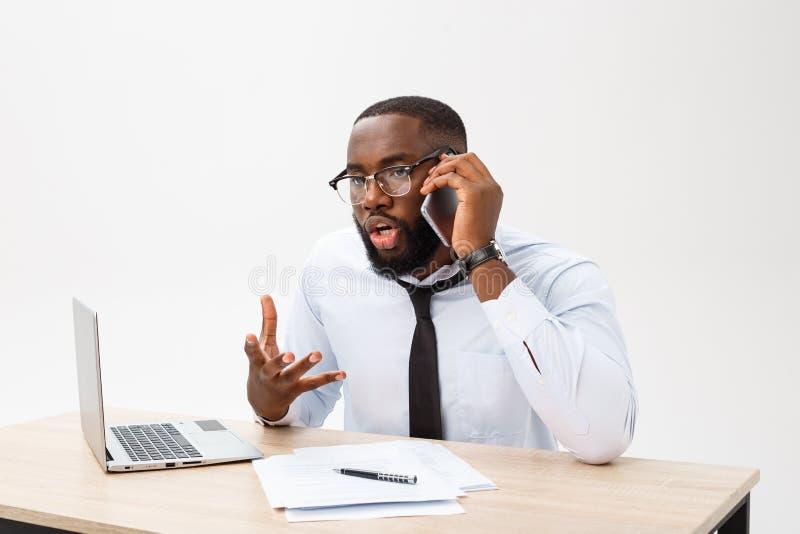 De teleurgestelde Afrikaanse zakenman wordt duizelig gemaakt het spreken op telefoon en verward Hij voelt totaal meningsverschil  stock afbeeldingen