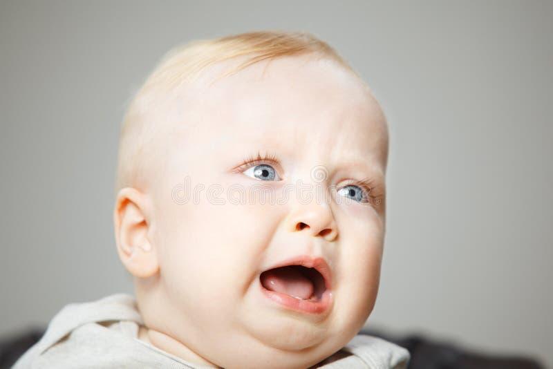 De teleurgestelde blonde babyjongen schreeuwt harde portretfoto royalty-vrije stock afbeelding