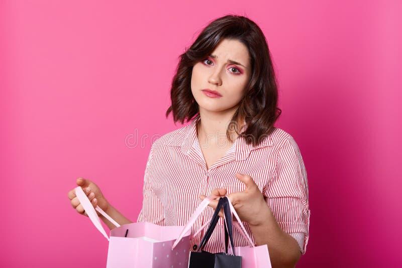 De teleurgestelde donkere haired vrouw, draagt toenam blouse, houdt geopende zak Het mooie brunette kijkt ongelukkig, niet houdt  royalty-vrije stock foto