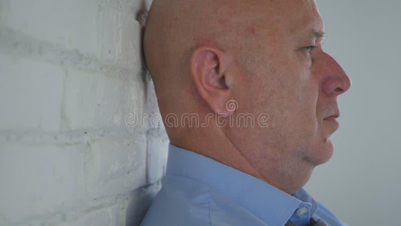De teleurgestelde Zakenman in Bureauverblijf dichtbij een Muur en denkt Peinzend stock afbeelding