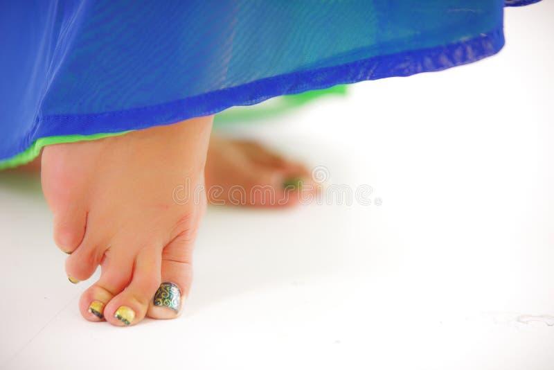 De tenen van close-upbellydancers, blauw gekleurde rok dragen en de geschilderde spijkers, het presteren die stellen, witte studi royalty-vrije stock foto's