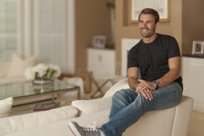 De terloops geklede man geniet van een ogenblik alleen in zijn woonkamer royalty-vrije stock fotografie