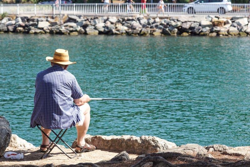 De teruggetrokken hogere mens geniet van vissend van een pijler in de rivier stock afbeeldingen