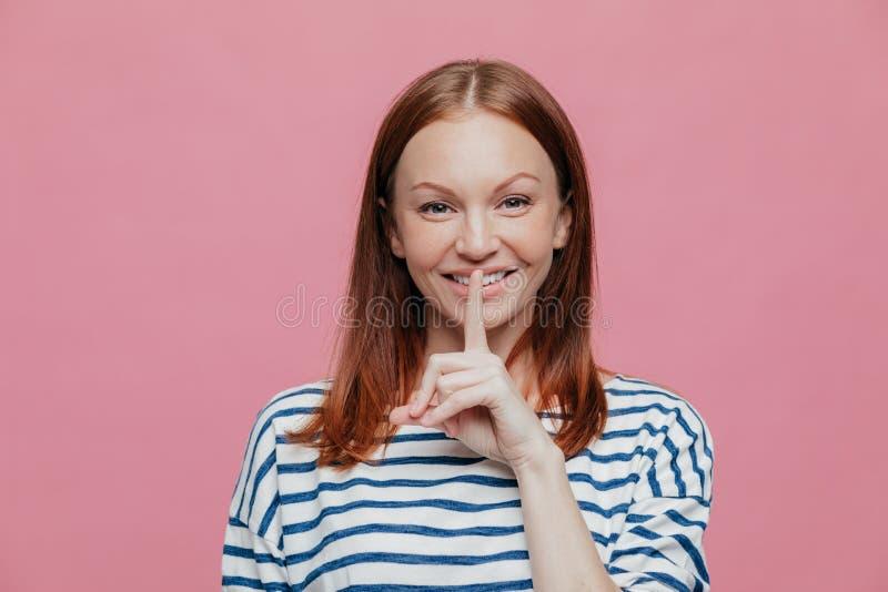 De tevreden aantrekkelijke vrouw met bruin haar, zachte glimlach, houdt wijsvinger op lippen, toont stiltegebaar, gekleed in gest stock afbeelding