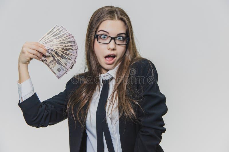 De tevreden, opgewekte jonge bedrijfsdievrouw toont een stapel van geld, op witte achtergrond wordt geïsoleerd Het meisje heeft h stock foto's