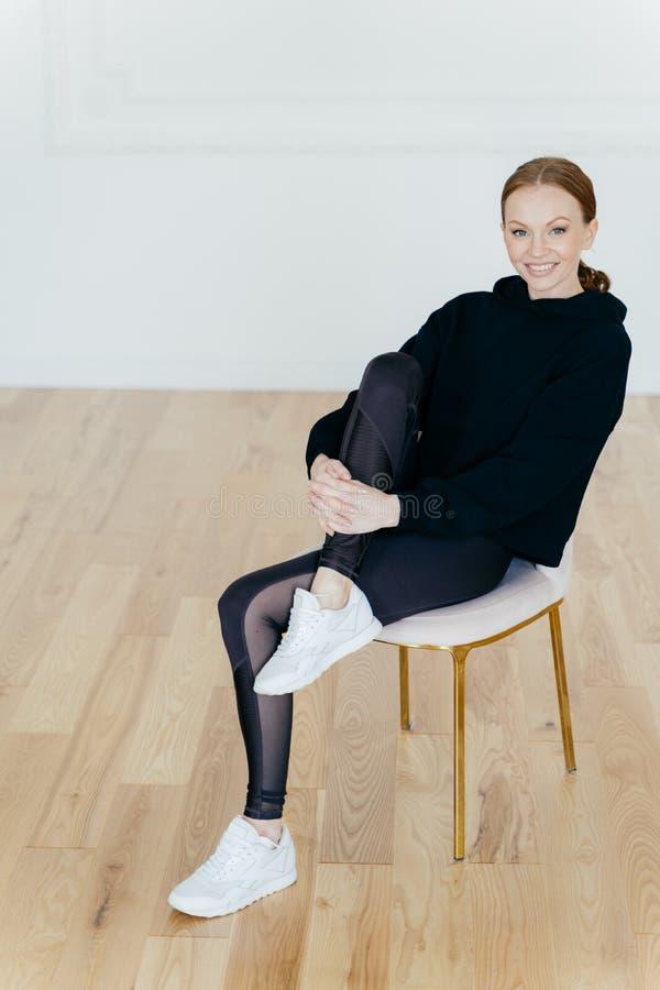 De tevreden vrouw met gember gekamd haar, heeft prettige glimlach, heft been op en houdt hand op knie, stelt op stoel in studio,  royalty-vrije stock afbeeldingen