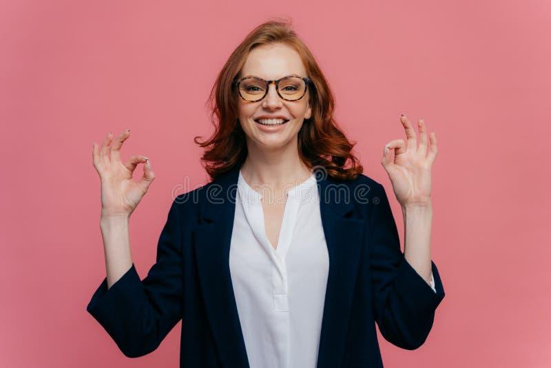 De tevreden vrouwelijke financier maakt o.k. gebaar met beide handen, heeft prettige glimlach op gezicht, draagt formele slijtage royalty-vrije stock fotografie