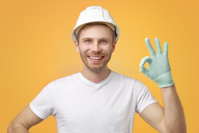 De tevreden zekere Europese mens met brede eenvormige glimlach, toont o.k. gebaar, gekleed in t-shirt en bouwhelm royalty-vrije stock foto's