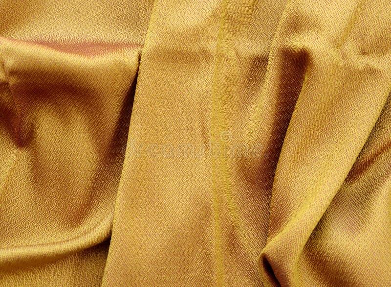 De textuur dichte omhooggaand van de zijde gouden stof stock fotografie