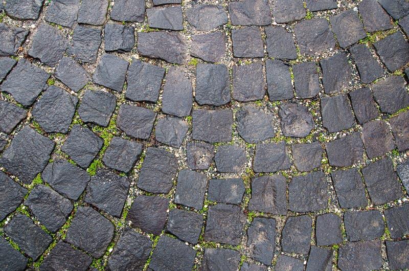 De textuur van de steenbestrating Het graniet cobblestoned achtergrond Samenvatting van oud keiclose-up naadloos praag royalty-vrije stock foto's
