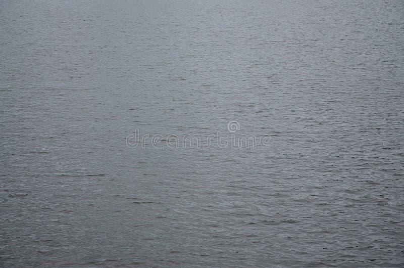 De textuur van donker die rivierwater onder de invloed van wind, in perspectief wordt gestempeld Horizontale imag stock fotografie