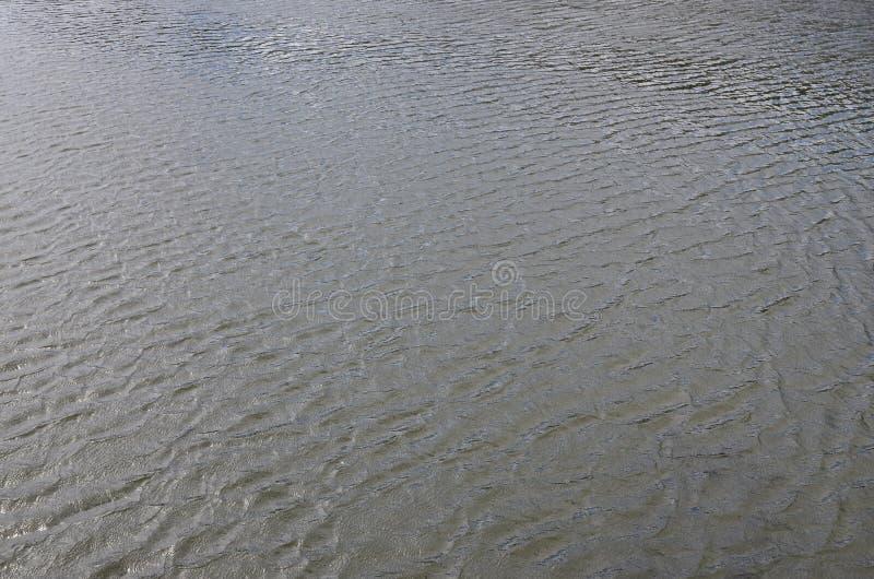 De textuur van donker die rivierwater onder de invloed van wind, in perspectief wordt gestempeld Horizontale imag stock foto's