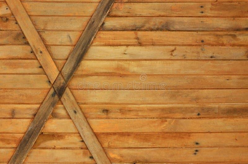De textuur van doorstane houten muur Textuur van een oude omheining van horizontale oranje houten planken met dwars-raad stock foto's
