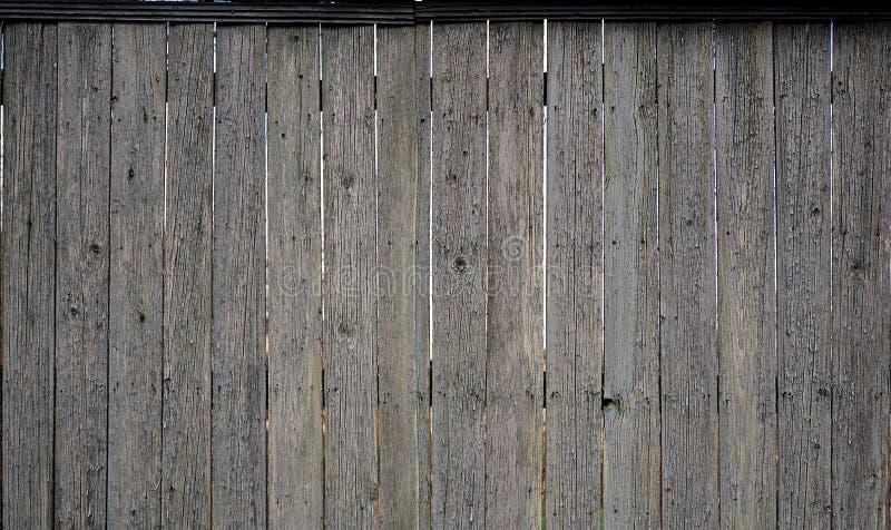 De textuur van een oude rustieke houten die omheining van vlak verwerkte raad wordt gemaakt Gedetailleerd beeld van een straatomh stock afbeelding