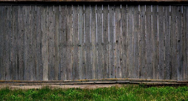De textuur van een oude rustieke houten die omheining van vlak verwerkte raad wordt gemaakt Gedetailleerd beeld van een straatomh stock foto