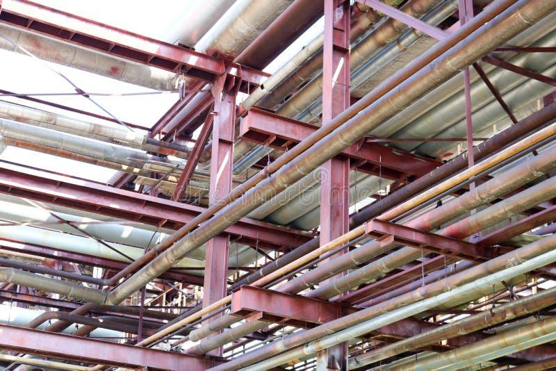De textuur van een pijpleidingsviaduct met ijzer roestige pijpen voor het pompen van vloeistoffen met afzet en afvoerkanalen bij  royalty-vrije stock afbeeldingen