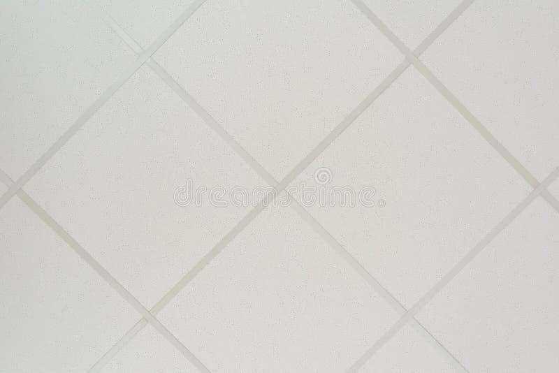 De textuur van een vals plafond uit vierkante platen bestaan en een het leiden profiel die van de diagonale regeling stock foto
